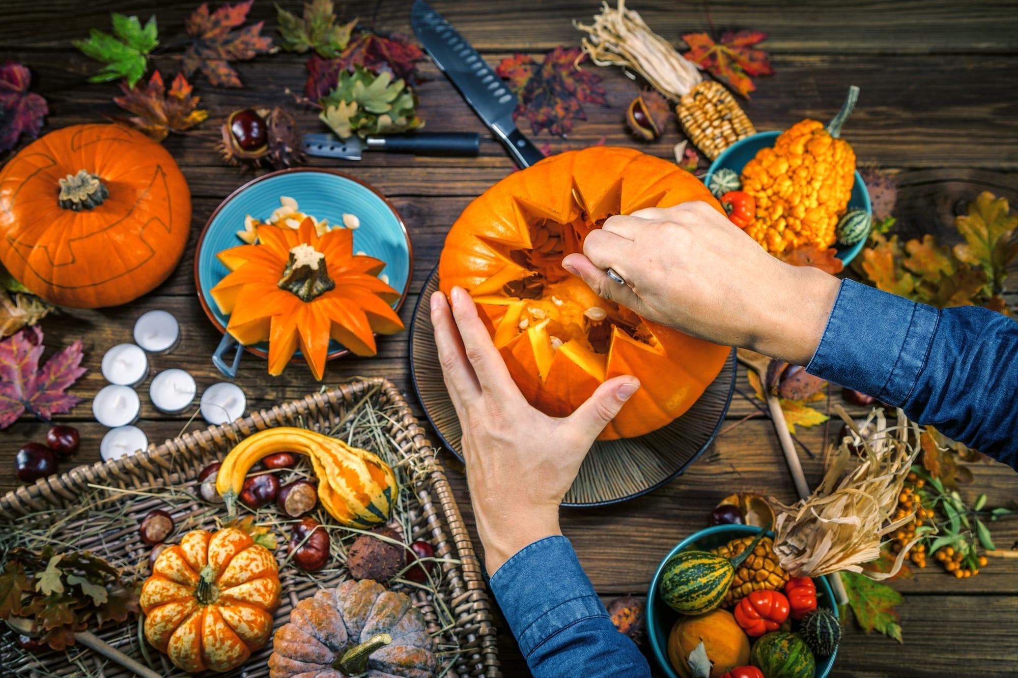 A person creates a pumpkin display